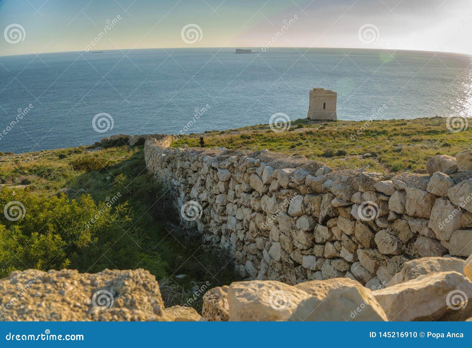 Landskap med den tipic kalkstenväggen och Tal Hamrija tornet