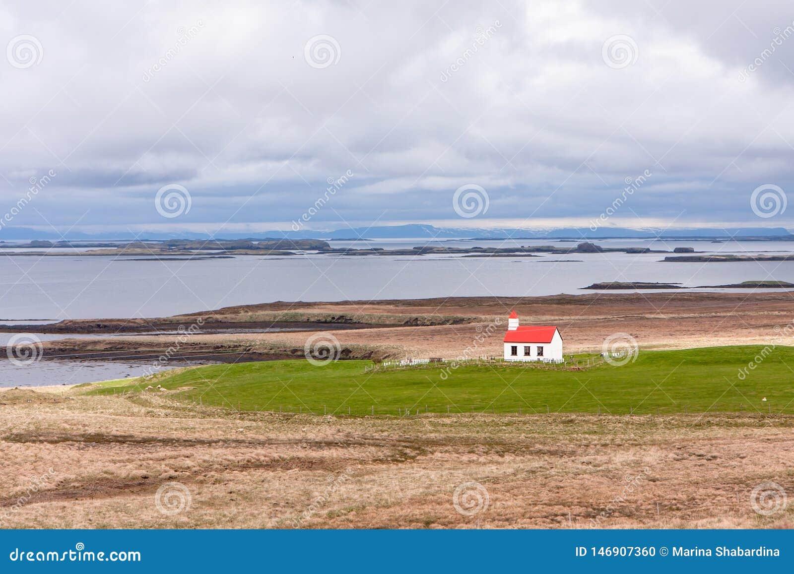 Landskap med en sikt av huset vid havfjärden, berget och himlen