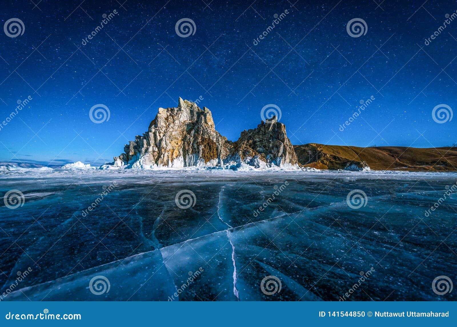 Landskapet av Shamanka vaggar och stjärnan på himmel med naturlig brytande is i djupfryst vatten på Lake Baikal, Sibirien, Ryssla