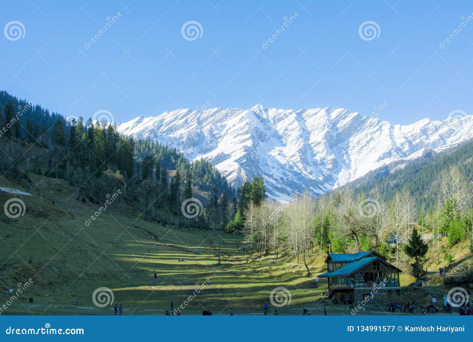 Landskapsikt av dalen med snöberget i bakgrund och det greenfiled och trähuset i förgrund