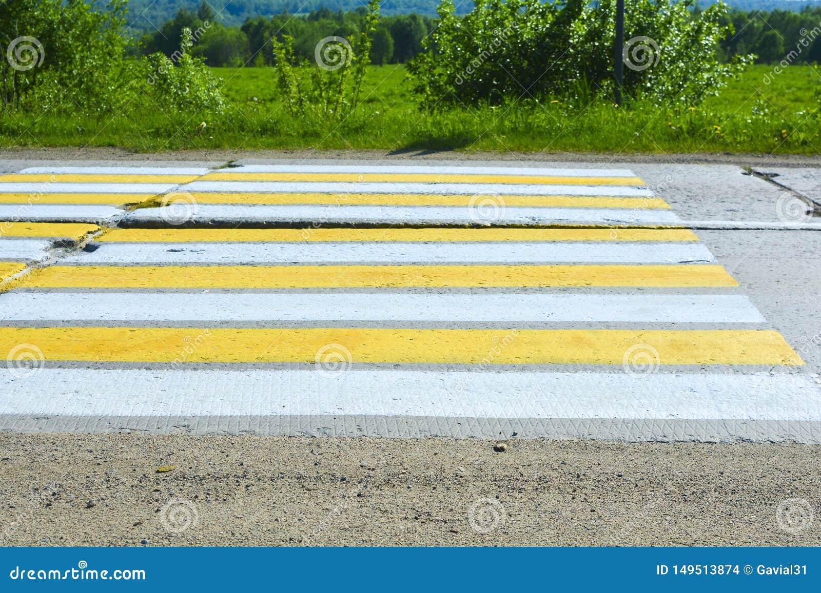 Landstraße von Betonplatten Fußgängercrossing over eine Betonstraße Weiße und gelbe Streifen auf der Straße