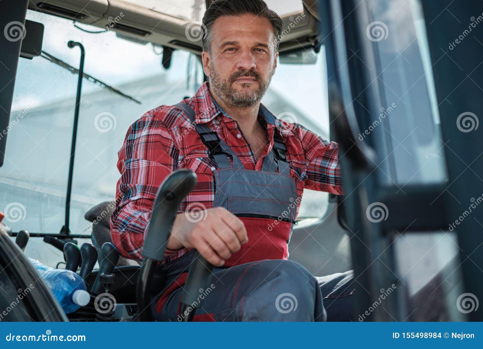 Landwirt, der an einem modernen Traktor arbeitet