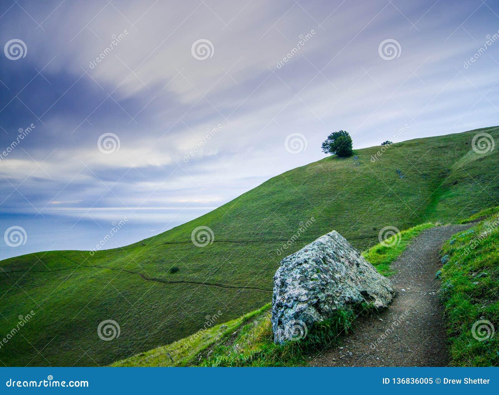 Lange Belichtungsphotographie mit beweglichen Wolken, einem Weg, der weg führen, grünen Hügeln und glattem Ozean