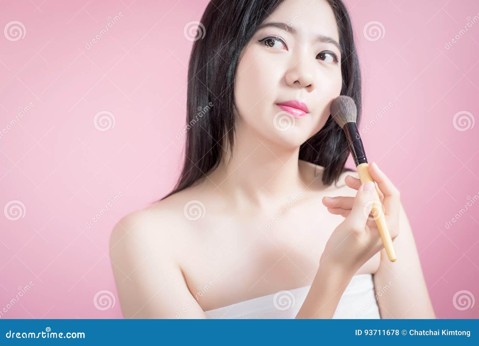 Lange haar Aziatische jonge mooie vrouw die kosmetische poederborstel op vlot gezicht over roze achtergrond toepassen Natuurlijke