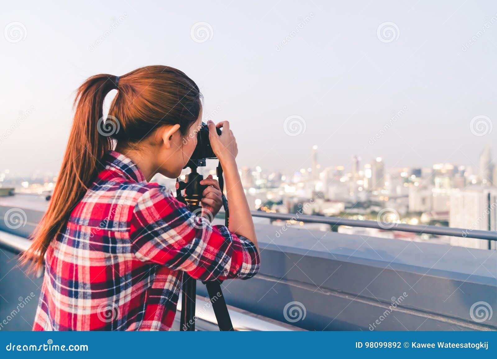 Lange haar Aziatische vrouw die cityscape foto bij de bouw van dak in laag lichtsituatie nemen Fotografie of hobbyconcept Met exe