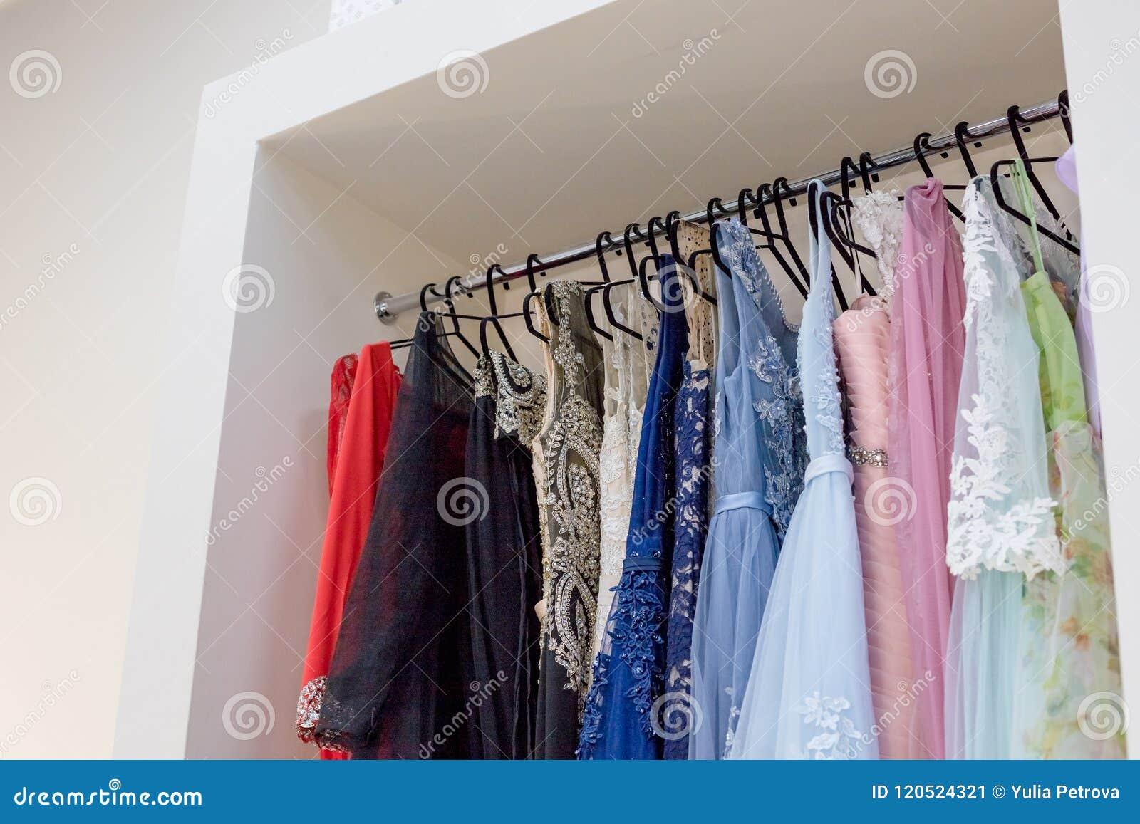 lange kleider auf aufhänger in der kleidermiete glättend
