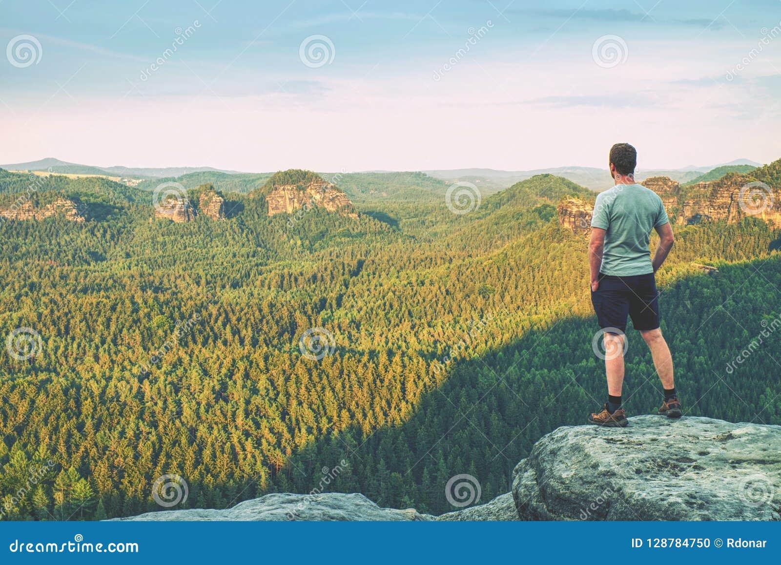 Lange mens in openluchtklerentribunes alleen op de piek van rots