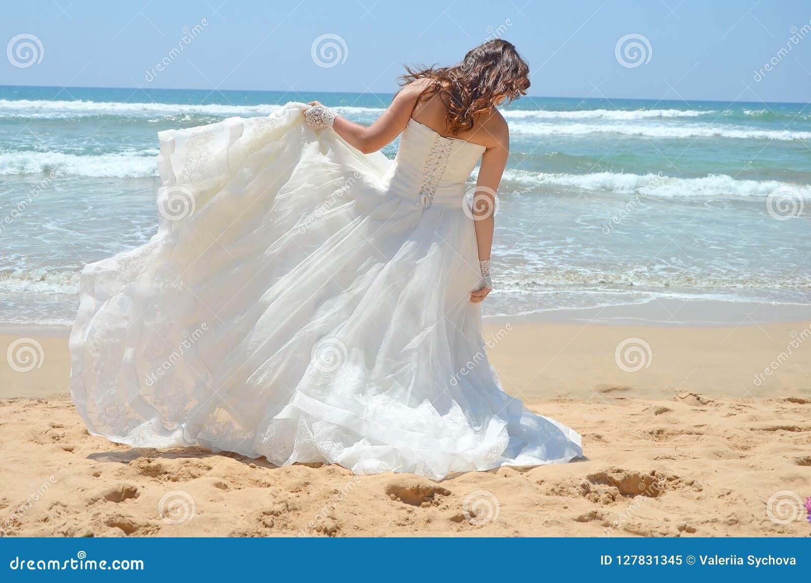 Langhaarige Brunettebraut richtet ihr Kleid gerade, das auf dem Sand, der Strand auf dem Indischen Ozean steht Hochzeit und Flitt