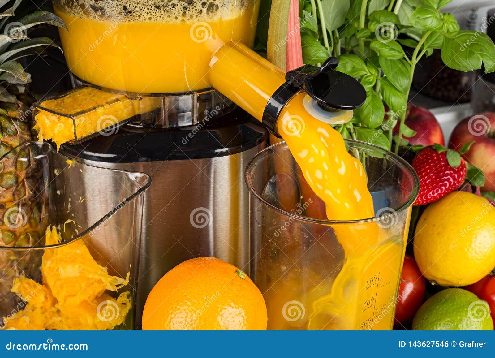 Langzame juicer in keuken met vele fruit en plantaardige oranje achtergrond van het de levensstijlconcept van het vitaminesap gez