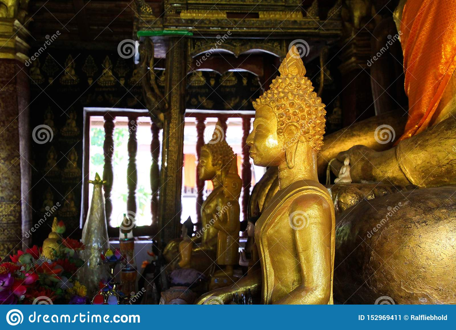 LANIÈRE DE LUANG PRABANG WAT XIENG, LAOS - 17 DÉCEMBRE 2017 : Statues de Bouddha à l intérieur du temple illuminé par lumière du