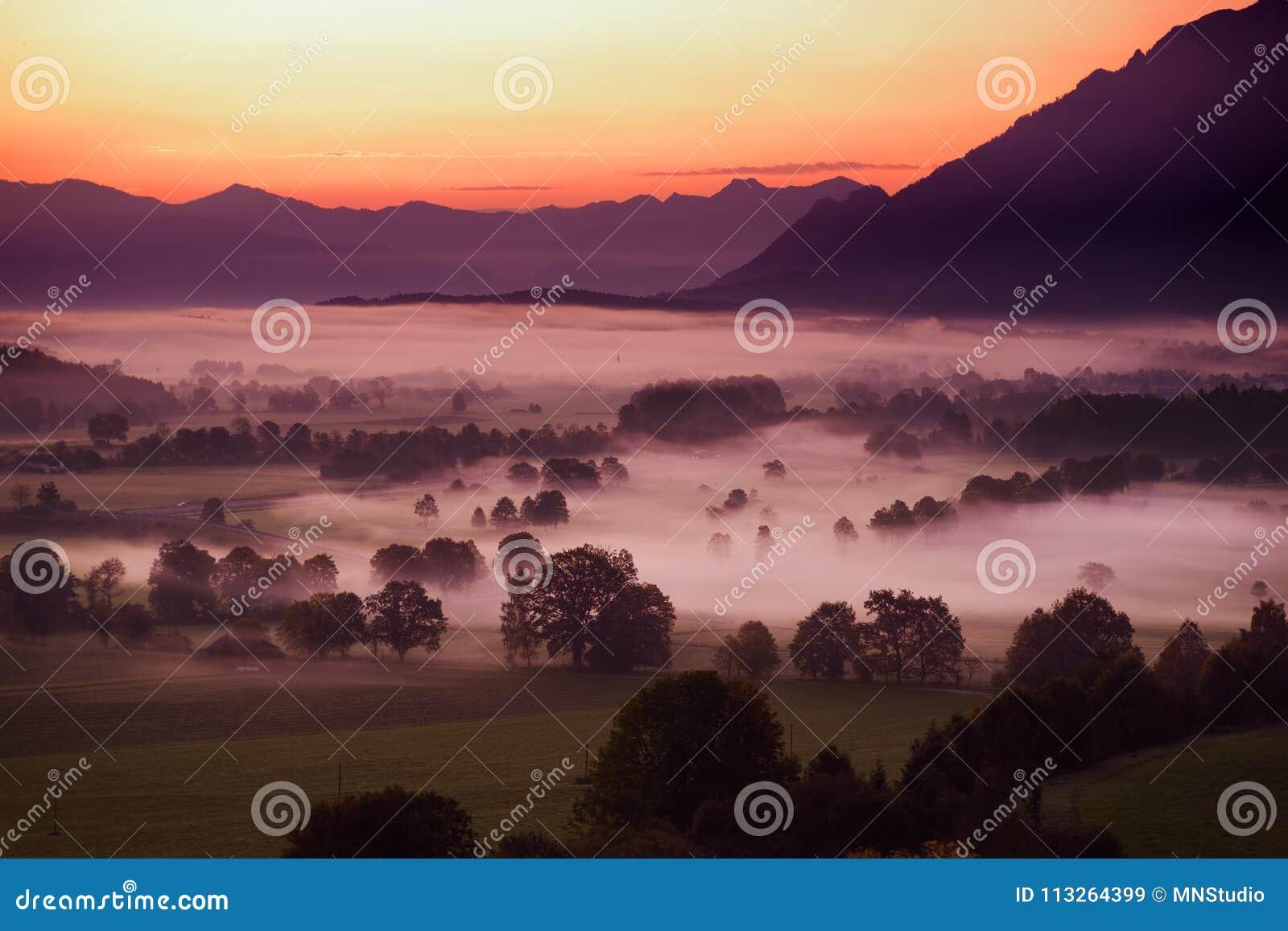 Lansdcape stupéfiant de matin du petit village bavarois couvert en brouillard Vue scénique des Alpes bavarois au lever de soleil