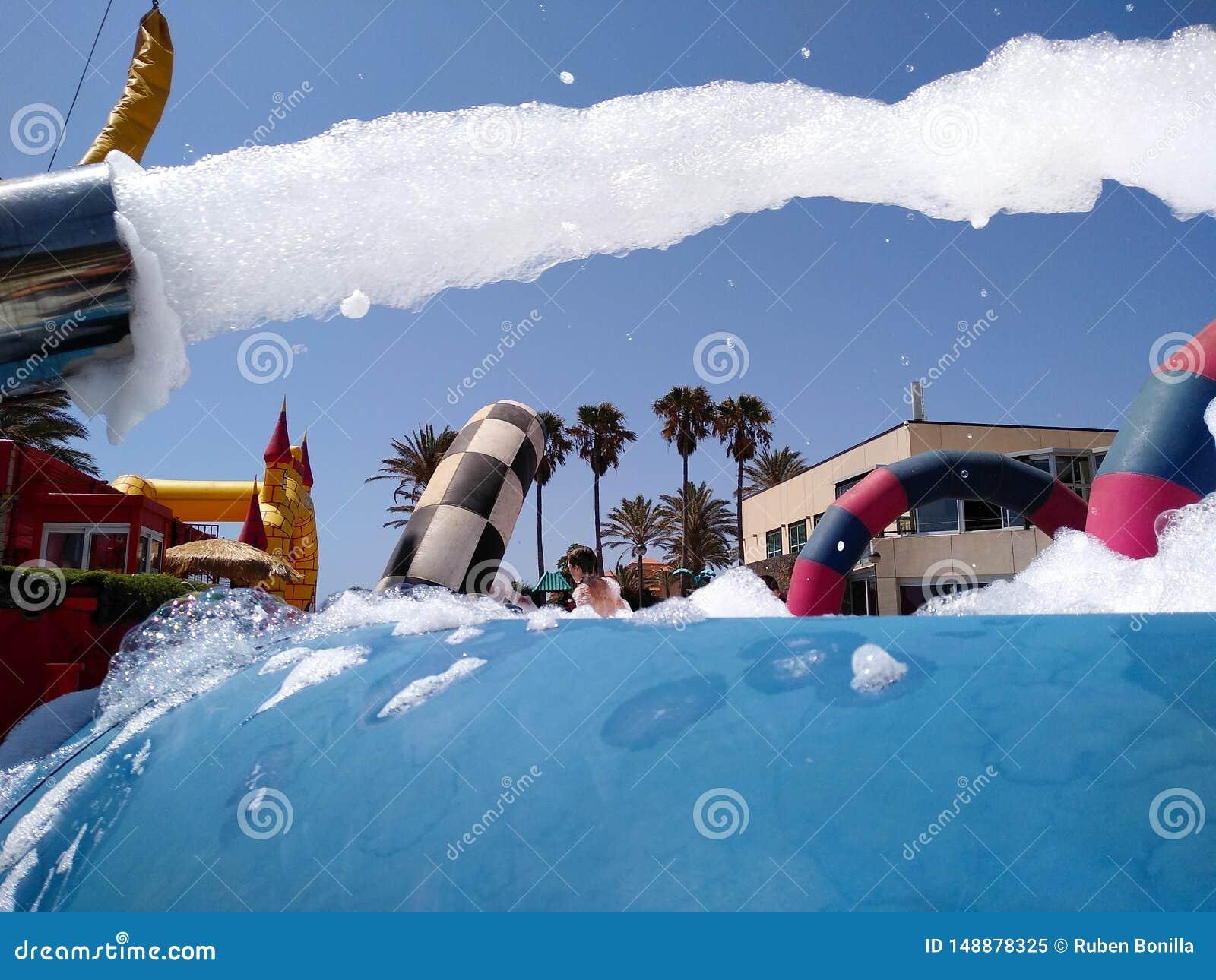 Lanserande vitt skum f?r roligt sommarparti fr?n en maskin till en p?l var den b?rande baddr?kten f?r folk f?r v?t mot det varmt