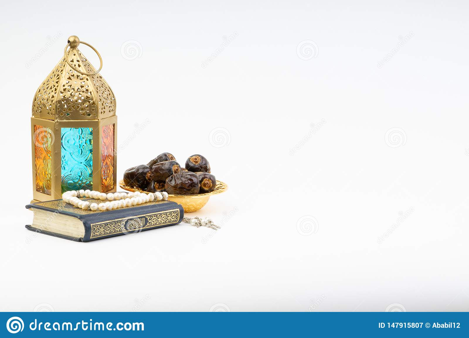 Lantern, Dates, Koran and Rosary on white background with selective focus and crop fragment