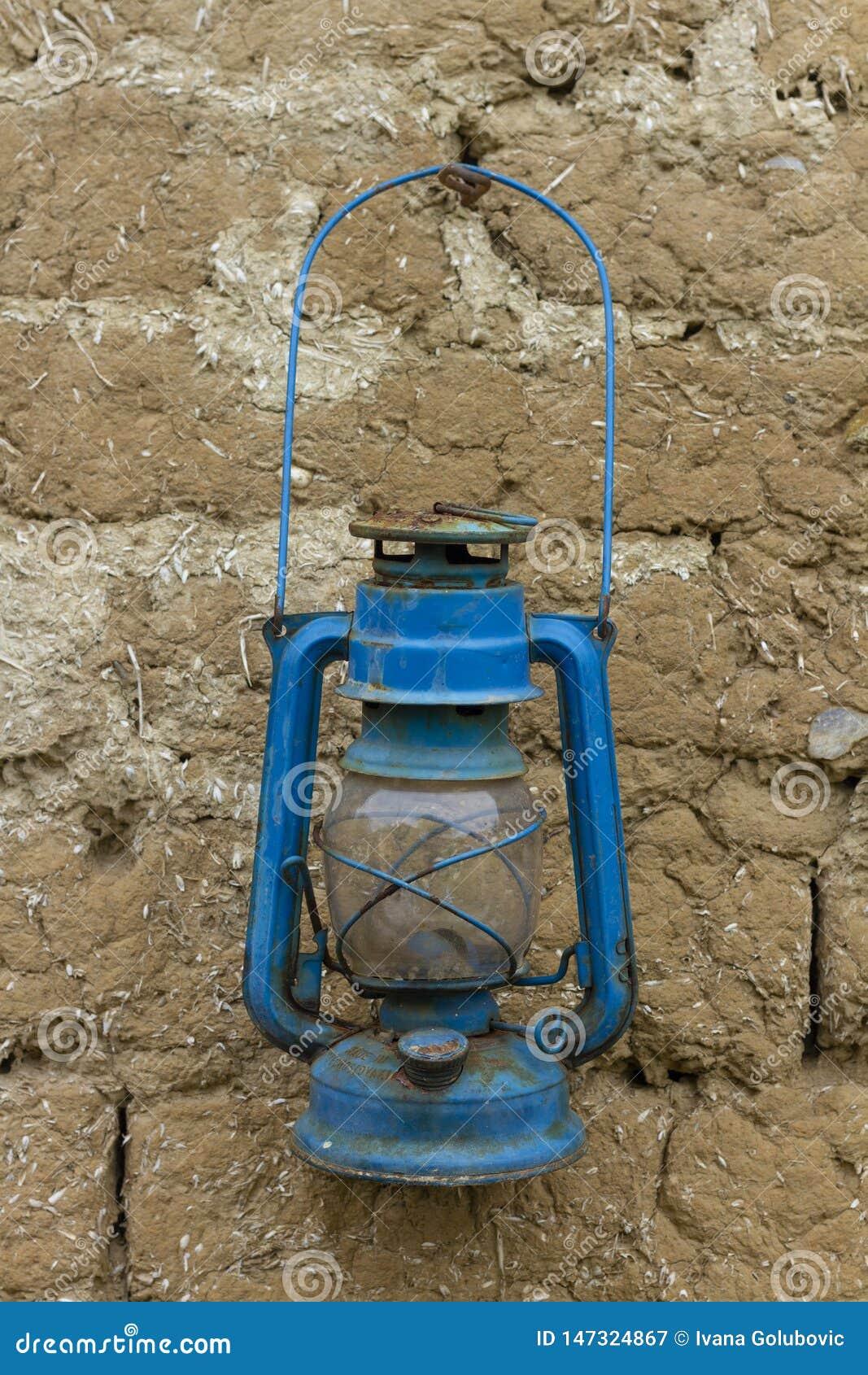 Lanterna azul oxidada velha do petróleo em uma parede de tijolo da lama