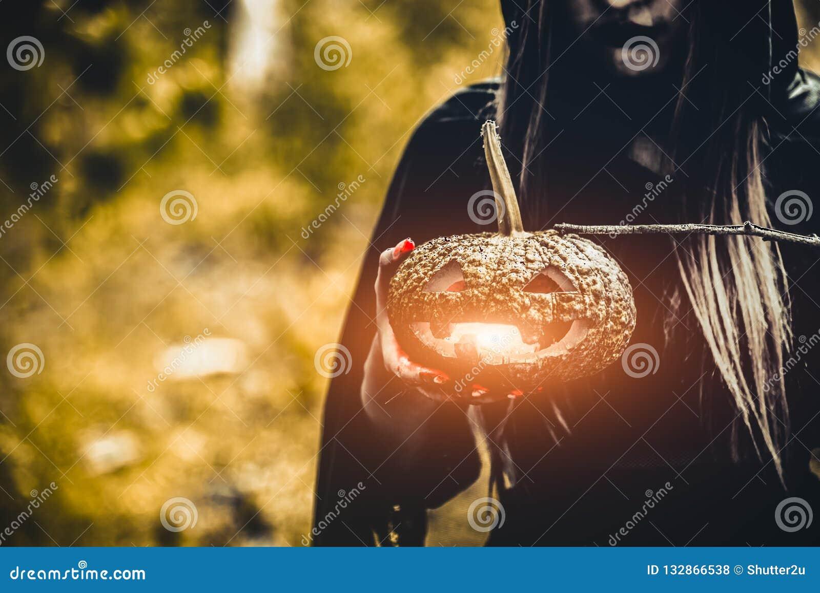 Lanterna da abóbora na mão da bruxa Abóbora da terra arrendada da mulher adulta na obscuridade