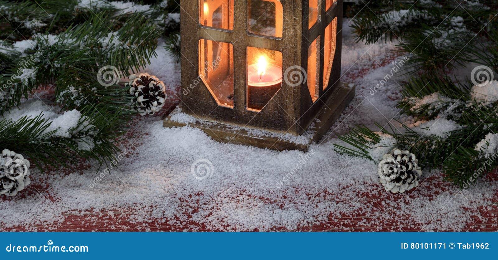 Lanterna do vintage com vela ardente em b de madeira vermelho rústico nevado