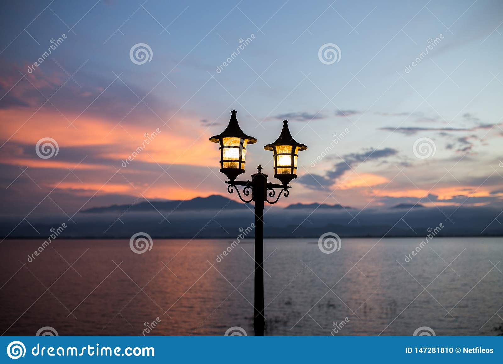 Lanterna leve no fundo da montanha e na escuridão crepuscular após atmosférico romântico do tempo do por do sol