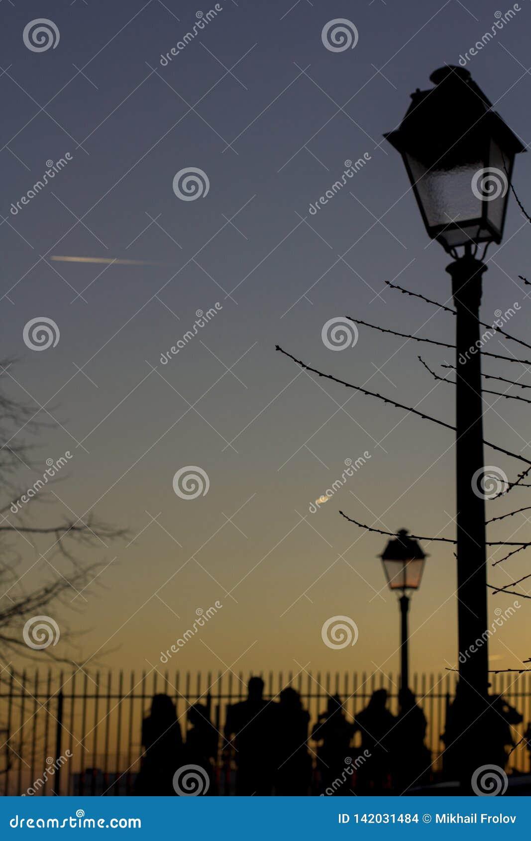 Lanternas da rua no por do sol No céu escuro, traços de aviões Silhuetas dos povos que amam a vista