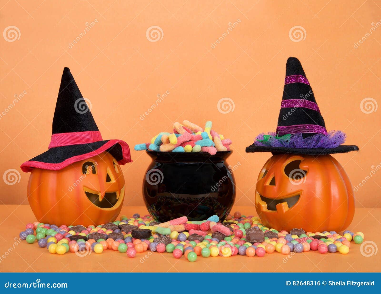 La caramella di Halloween worms straripando un calderone nero con le  caramelle dure e la caramella di cioccolato sulla tavola arancio 01841b544aa7
