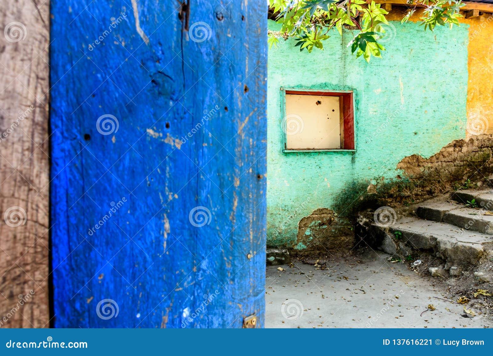 Lantlig öppen blå dörr & turkos & gul vägg