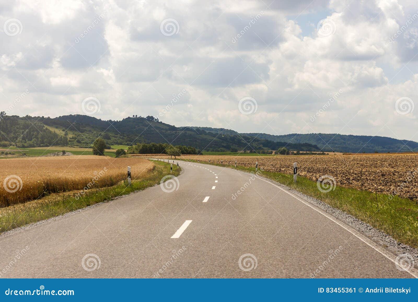 Lantlig väg för asfaltland i Tyskland till och med det gröna fältet