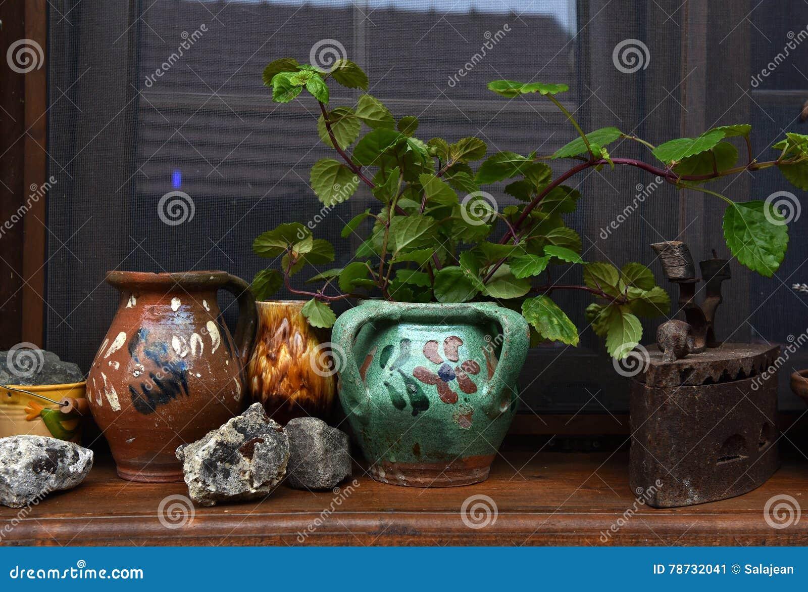 Lantligt husfönster och gammalt tillbringare, lerakrukor och järn