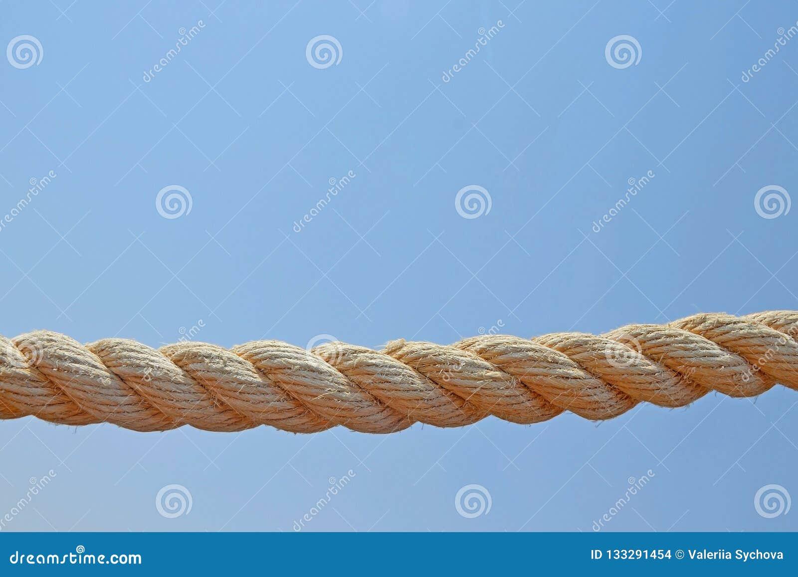 Lantligt krökt havsrep som hänger på bakgrund för blå himmel, beige bomull för att torka klädernärbild