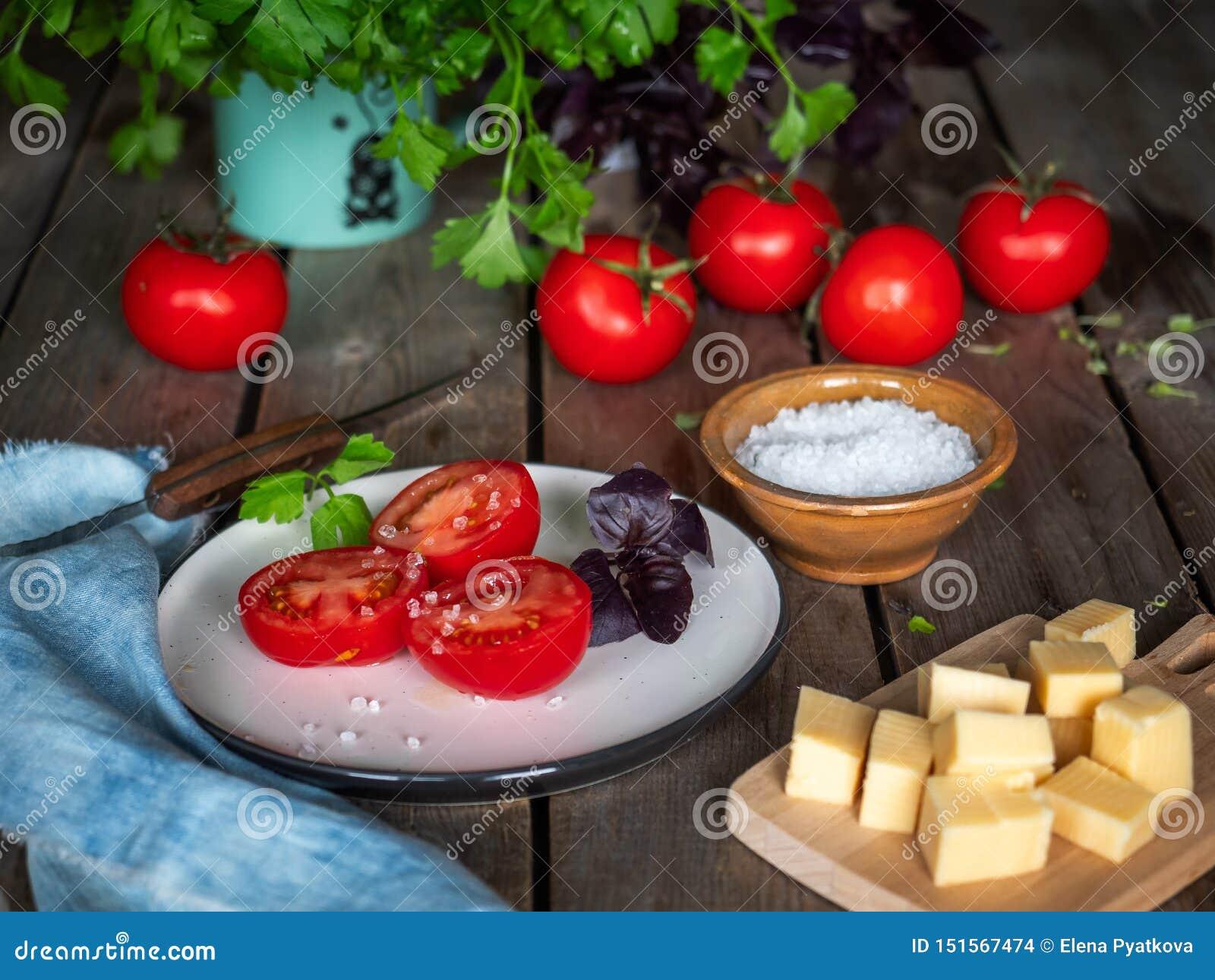 Lantligt skissa, en liten lunch av ost och röda tomater Persiljagräsplaner i ett keramiskt rånar, grov bomullstvillservetten på e