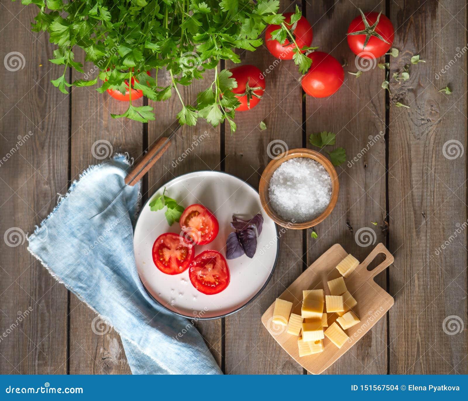 Lantligt skissa, lunch av huggen av ost på ett träbräde och röda tomater, en kvist av basilika Persiljagräsplaner, grov bomullstv