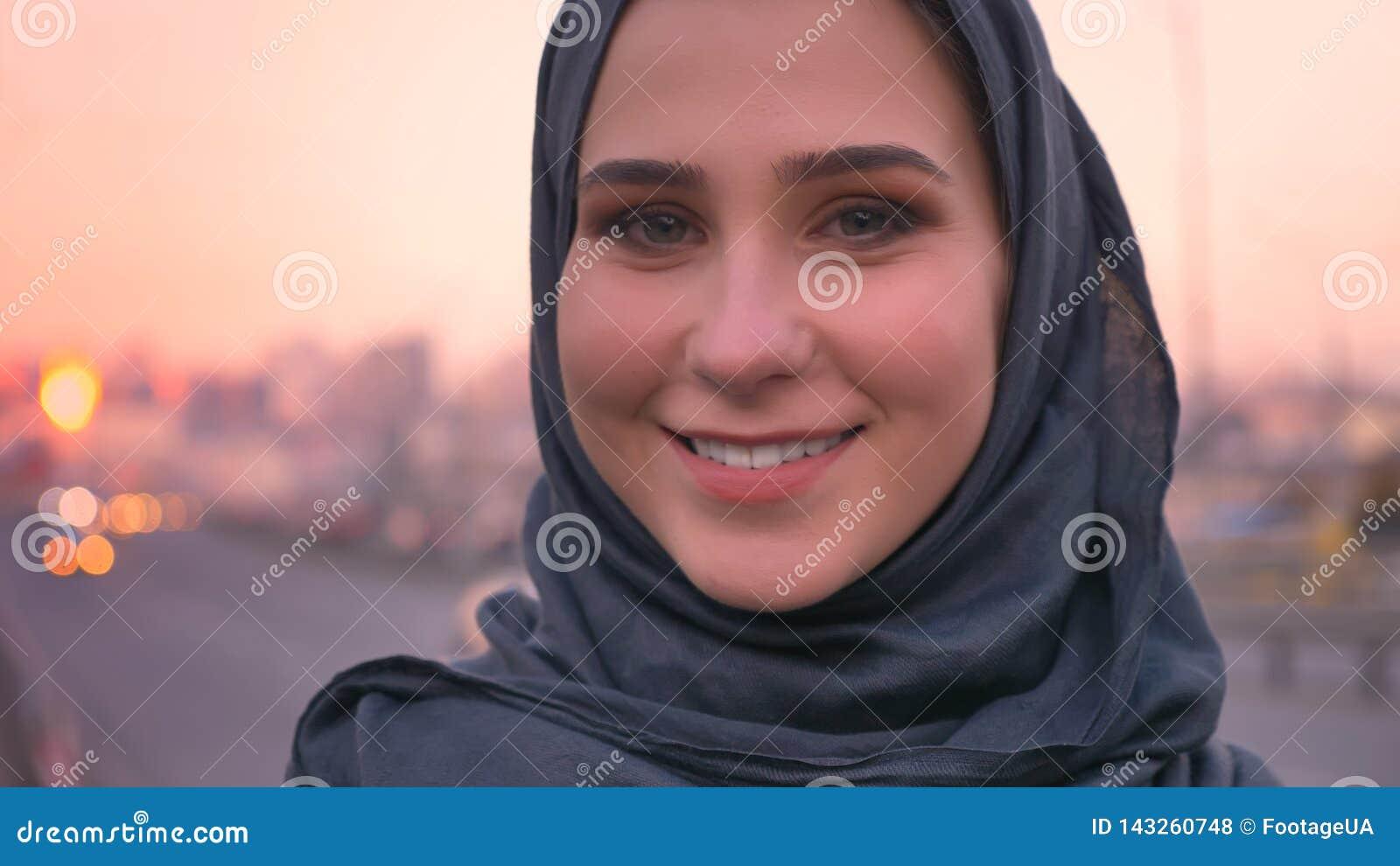 Lanzamiento del primer de la cara femenina atractiva joven en el hijab que mira derecho la cámara y que sonríe con el ambiente ur