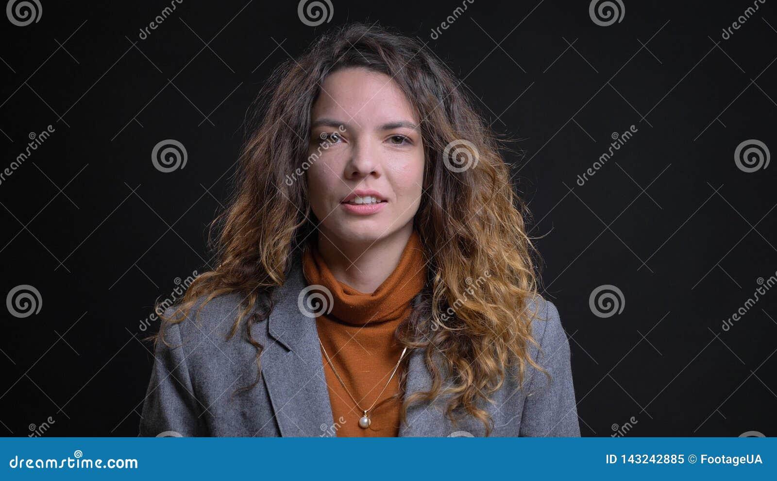 Lanzamiento del primer de la empresaria caucásica atractiva joven que está pensativa y que sonríe con el fondo aislado en negro