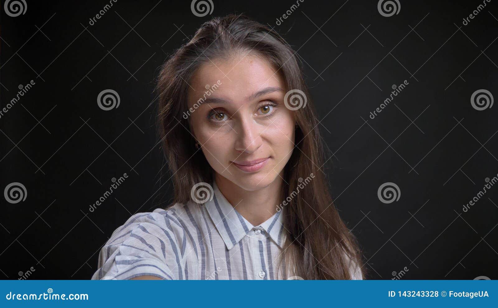 Lanzamiento del primer de la hembra atractiva joven que sostiene una cámara que mira derecho y que toma un selfie que sonríe feli