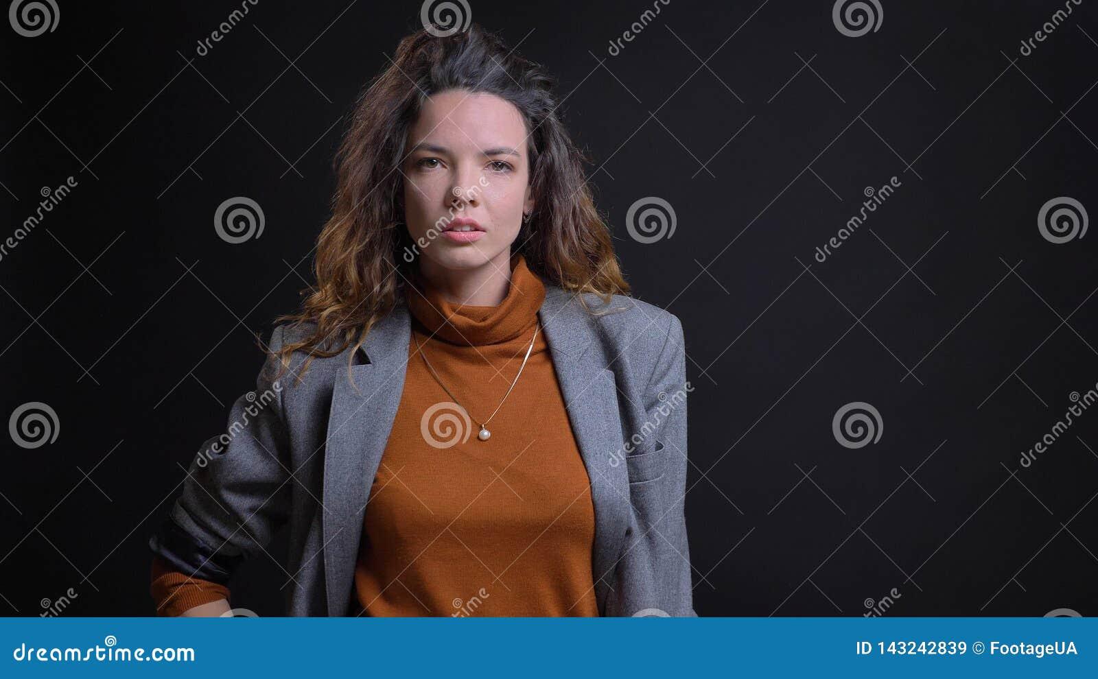 Lanzamiento del primer de la hembra caucásica atractiva joven que es furiosa y que tiene sus manos en las caderas que miran derec