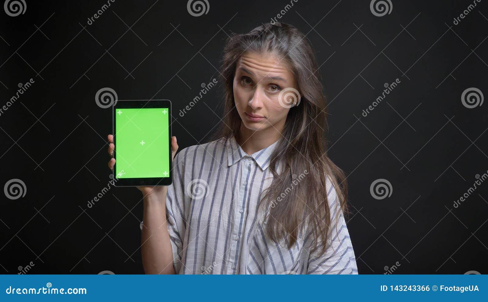 Lanzamiento del primer de mandar un SMS femenino caucásico bonito joven en la tableta y de mostrar la pantalla verde a la cámara