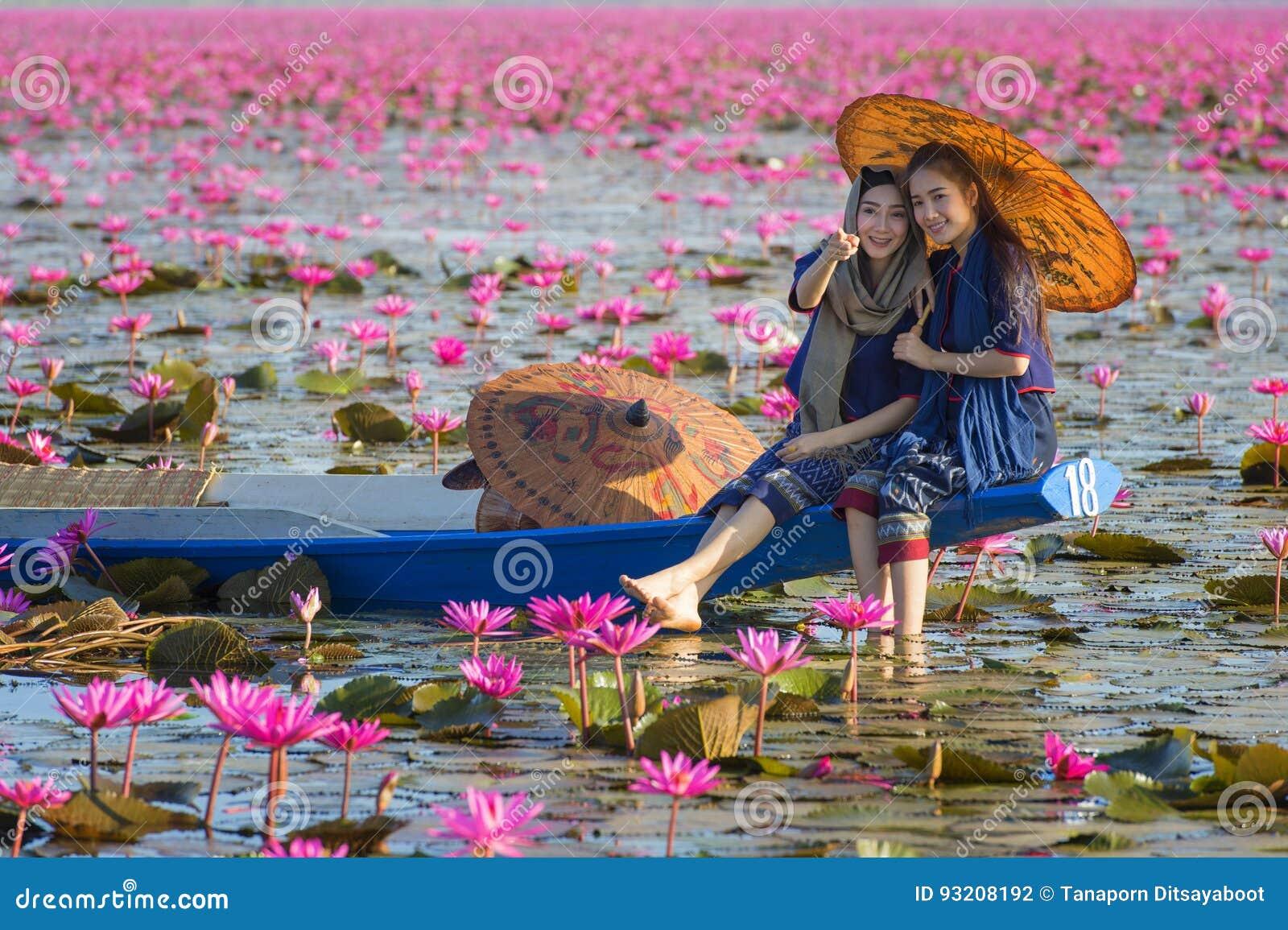 Laos kvinnasammanträde på fartyget i blommalotusblommasjön, kvinna som bär traditionellt thailändskt folk