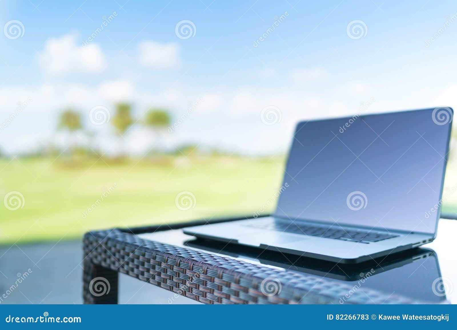 Lap-top στο υπόβαθρο θαμπάδων γηπέδων του γκολφ με το διάστημα, την επιχείρηση ή την εργασία αντιγράφων από οπουδήποτε την έννοια
