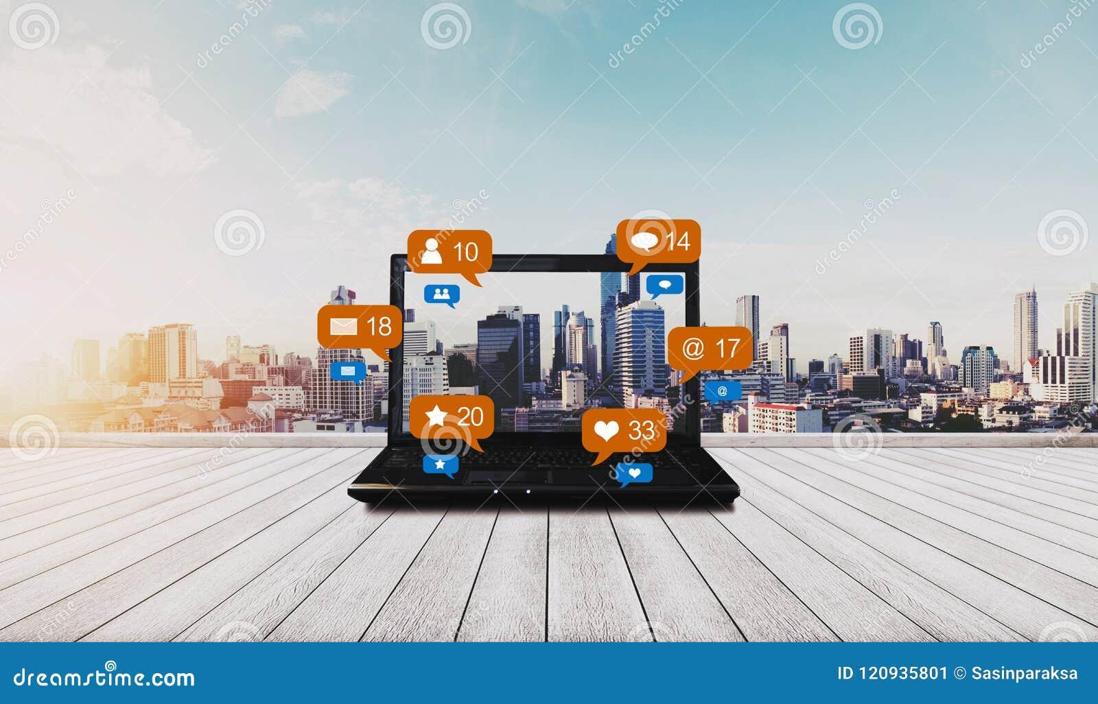 Lap-top υπολογιστών στο ξύλινο γραφείο και κοινωνικά μέσα με τα κοινωνικά εικονίδια ανακοίνωσης δικτύων, υπόβαθρο πόλεων