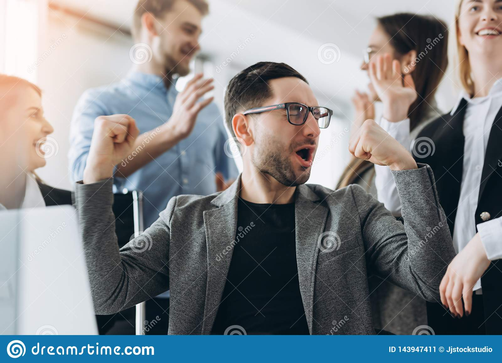Καθημερινοί νικητές Ομάδα ευτυχών επιχειρηματιών στην έξυπνη περιστασιακή ένδυση που εξετάζει το lap-top και Επιτυχία επίτευξης