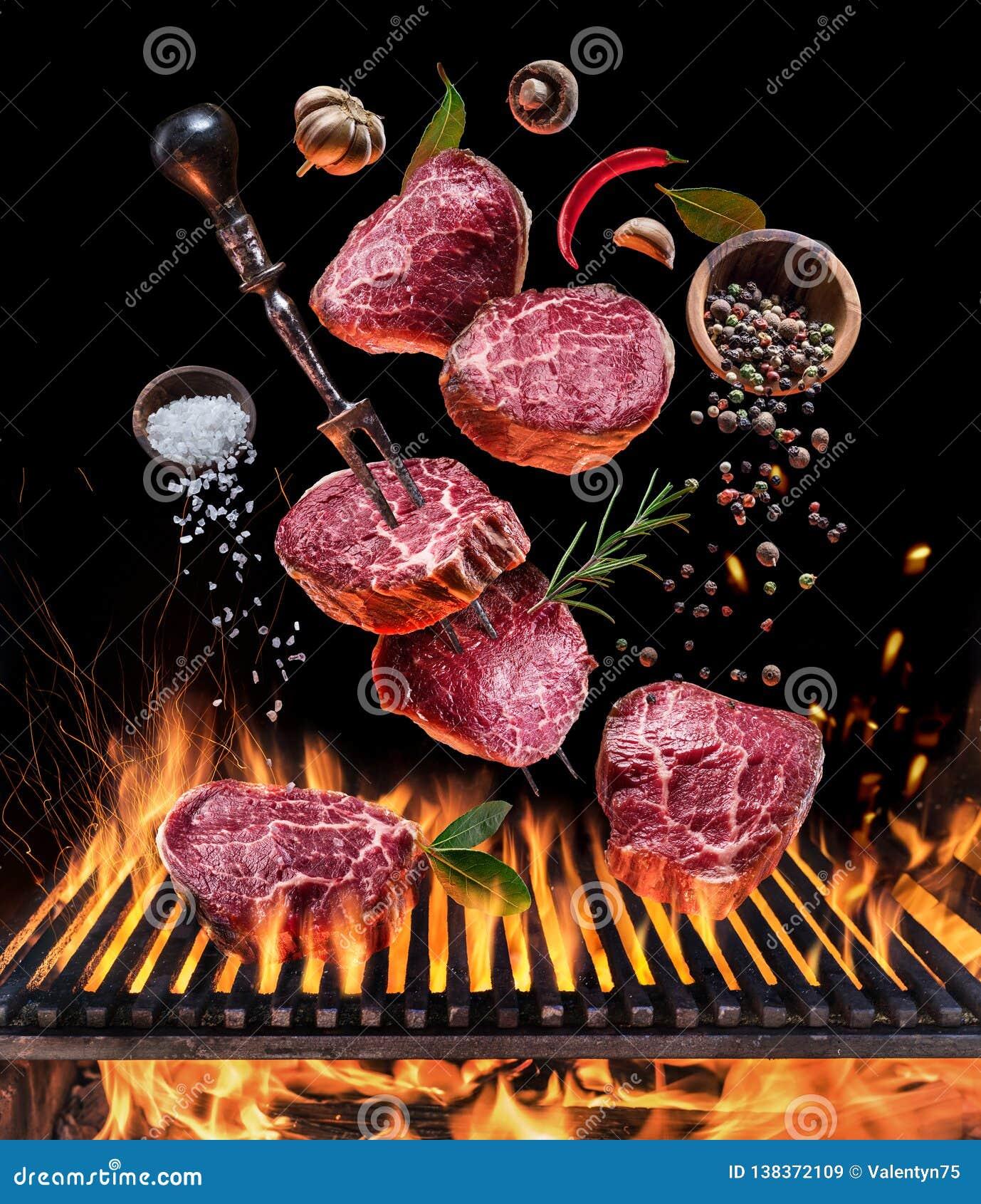 Lapje vlees het koken Conceptueel beeld Lapje vlees met kruiden en bestek onder brandende grillrooster