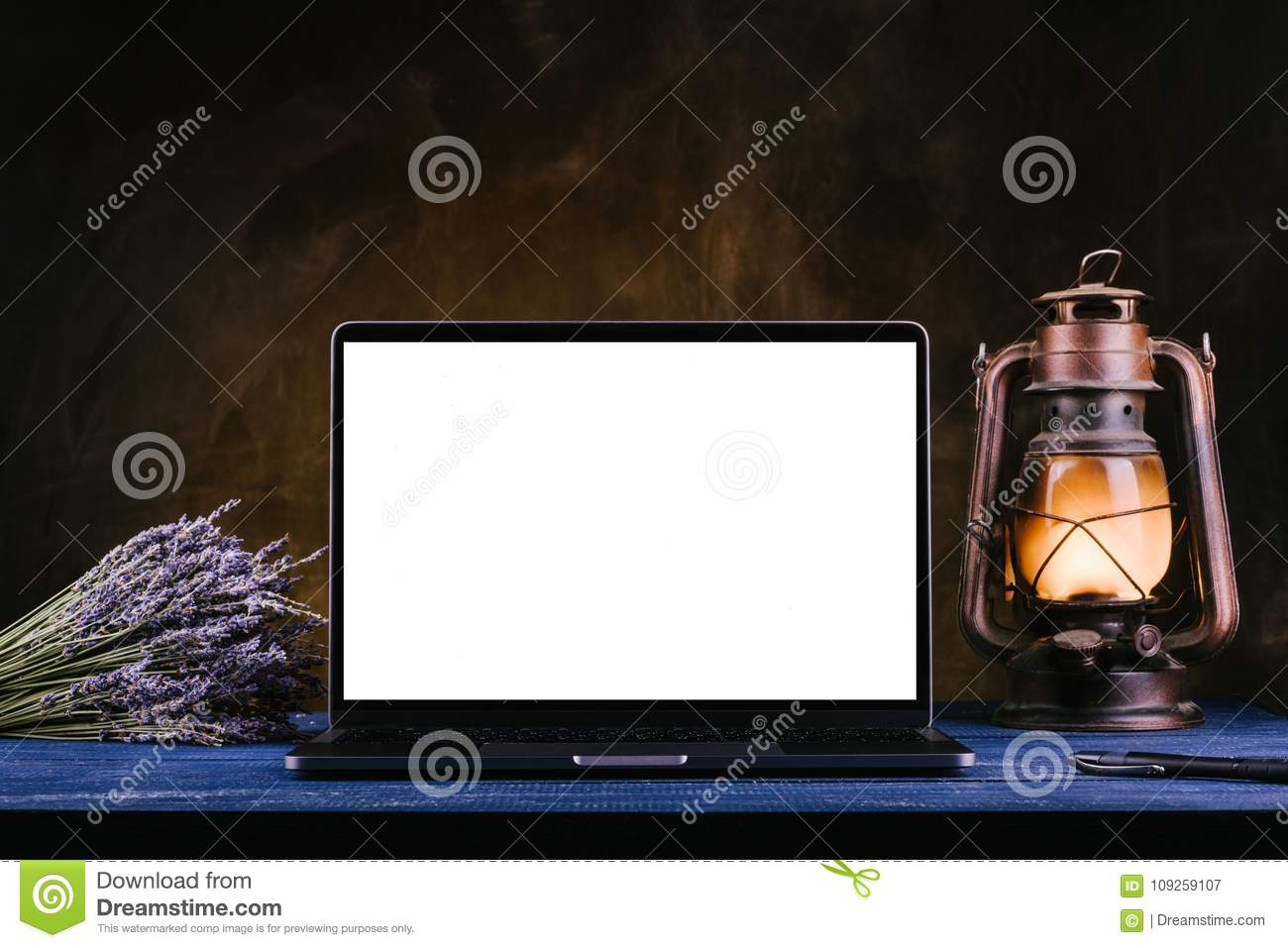 A laptop with a blank screen stands on a blue wooden table