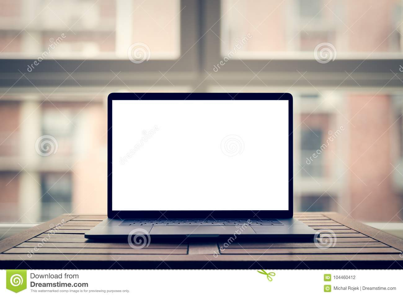 Laptop with blank screen on table in modern loft