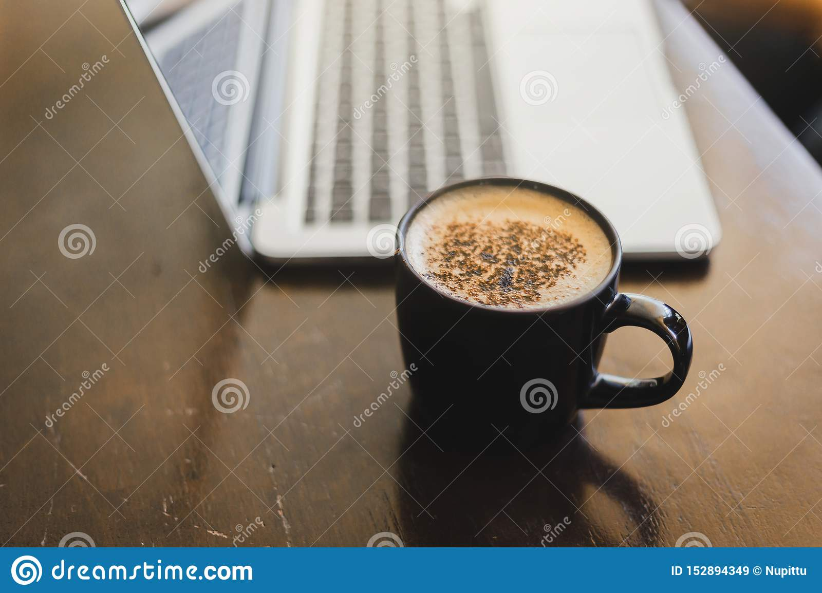 Laptop and coffee cup at his working place in Cafe. working other place for business.