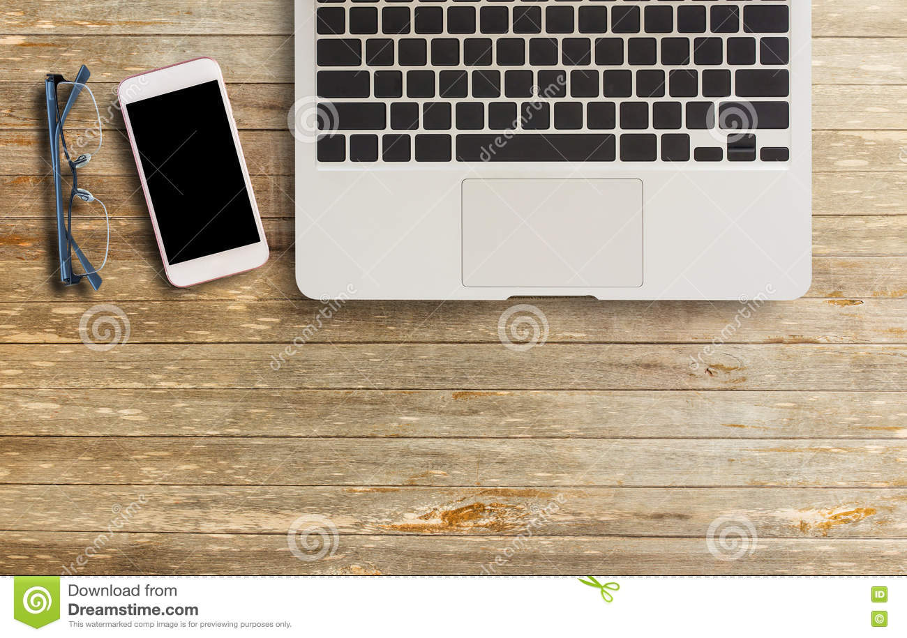 Laptop computer, glasses and smart phone on wood table