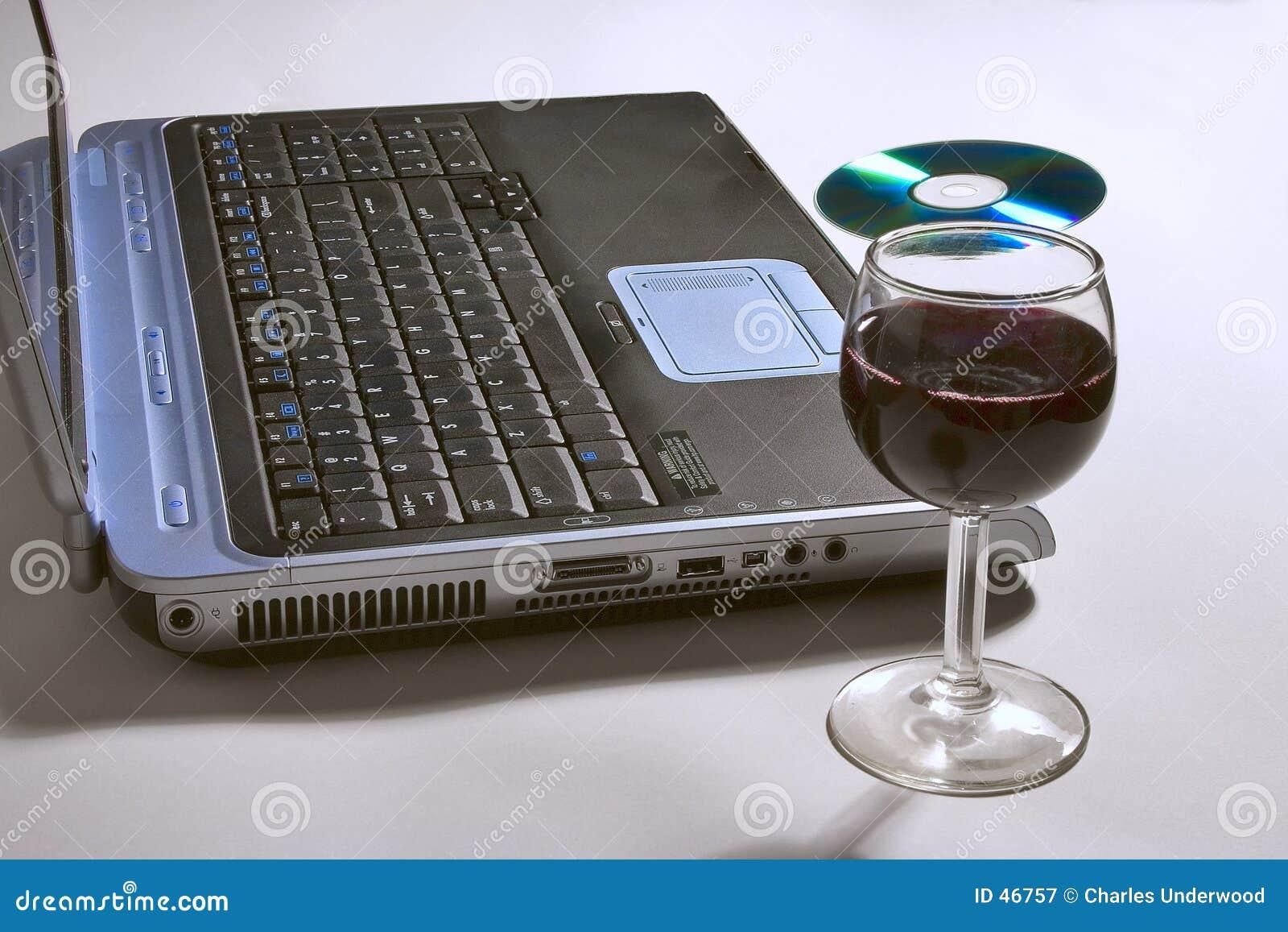 Laptop-Computer mit einem Glas Wein und CD.