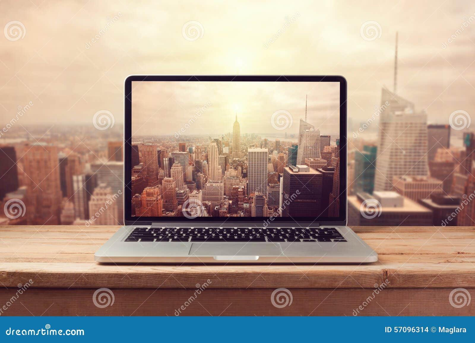Laptop computer over New York city skyline. Retro filter effect