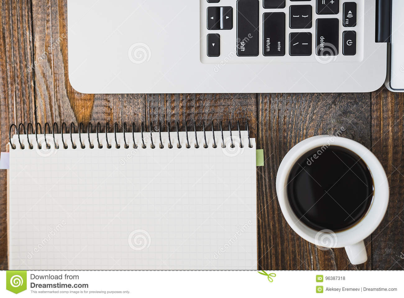 Laptop, a cup of coffee and a notebook lie on a wooden table. Horizontal frame