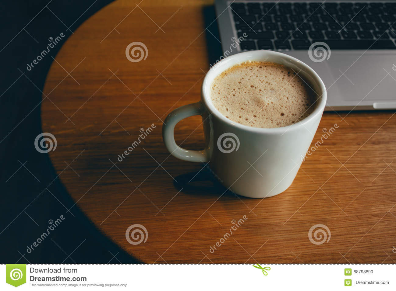 Laptop with cup of fresh coffee