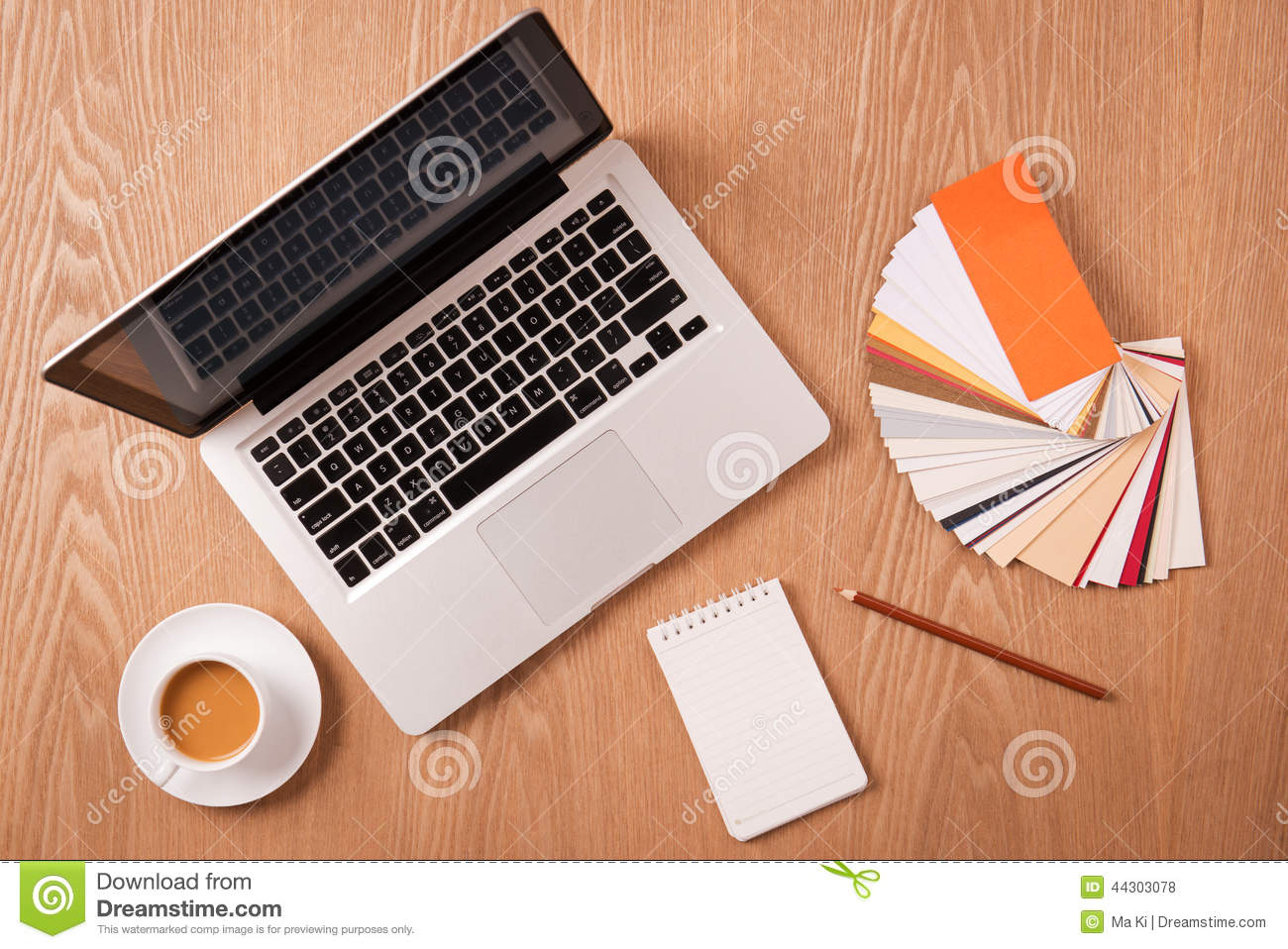 Laptop with designer color swatches and office supplies