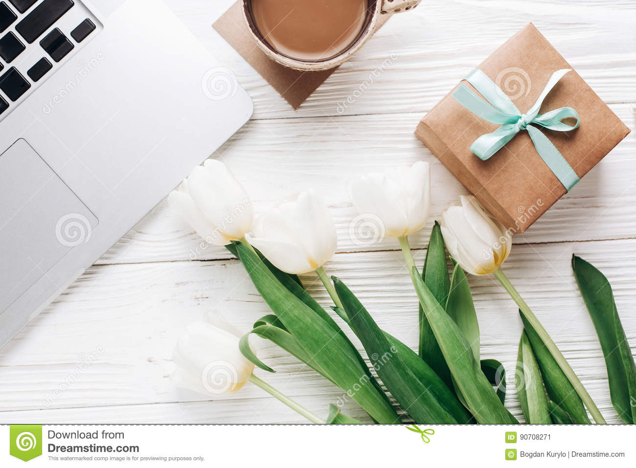 laptop with morning coffee and tulips and stylish gift box on white wooden rustic background. flat lay freelance, work gadgets wi