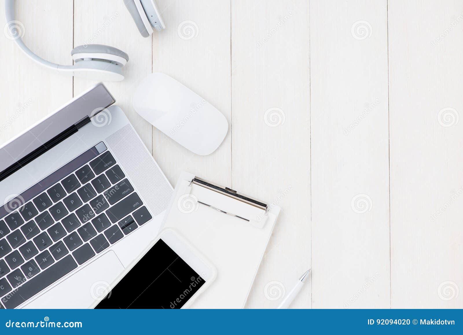 Laptop na bielu stole z hełmofonem i smartphone vi
